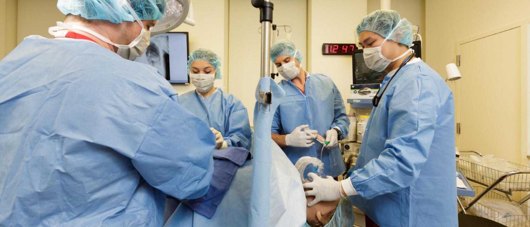 Doctor administering sedation drugs and while another administers oxygen to a patient in operating room.